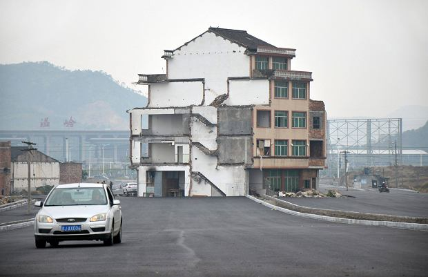 A car drives past a house which stands alone in middle of a newly built road in Wenling, Zhejiang province, November 22, 2012. An elderly couple refused to sign an agreement to allow their house to be demolished. They say that compensation offered is not enough to cover rebuilding costs, according to local media. Their house is the only building left standing on a road which is paved through their village. REUTERS/China Daily (CHINA - Tags: POLITICS SOCIETY) CHINA OUT. NO COMMERCIAL OR EDITORIAL SALES IN CHINA