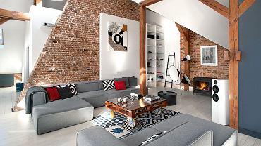 Ceglana ściana oddziela strefę dzienną od zabudowanej sypialni. Między sofami Carmo (BoConcept) stolik zaprojektowany w studio Cuns. Na ścianie obraz Małgorzaty Chmielowskiej.