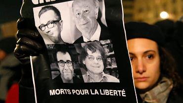 Mężczyzna z plakatem, na którym widać zdjęcia czterech z zastrzelonych rysowników i pracowników redakcji