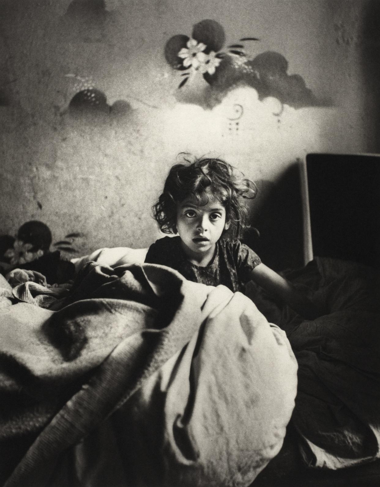 Sara, siedząca w łóżku w mieszkaniu w suterenie, z malowanymi szablonem kwiatami nad głową, Warszawa], ok. 1935-1937 (fot. Mara Vishniac Kohn, dzięki uprzejmości International Center of Photography)