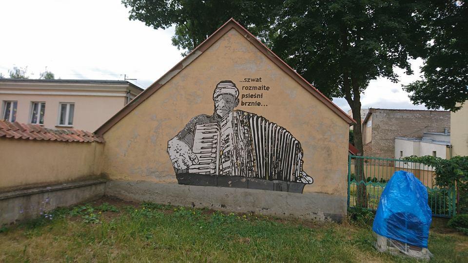 Mural w Ełku. Napis w języku mazurskim po polsku znaczy: Świat przeróżne gra melodie.