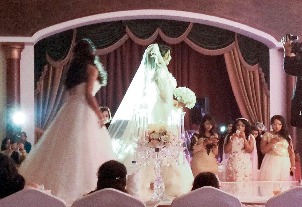 Zrobione ukradkiem zdjęcie z wesela. Wejście panny młodej, która zasiada na podwyższeniu, na specjalnie dekorowanym krześle (fot. Aleksandra Chrobak)