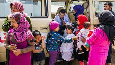 Uchodźcy w Libanie północnym, tuż przy granicy z Syrią. Rodzice z dziećmi czekają w kolejce do objazdowego lekarza