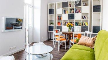 Otwarta strefa dzienna łączy salon i jadalnię. Tak jak w całym wnętrzu, tak i tu dominuje czysta biel. Ożywczy kolor wnosi kanapa z tapicerką w świeżym zielonym odcieniu.