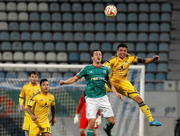 Legia Tomasz Jodlowiec, center, challenges for the ball against Edmar of Metalis, during a Europa League Group L soccer match between Metalist Kharkiv and Legia Warszawa  at Lobanovskiy stadium in Kiev, Ukraine, Wednesday, Oct. 22, 2014. (AP Photo/Sergei Chuzavkov) ZDJĘCIE DO WKŁADKI: DGWRP Gazeta WyborczaSport