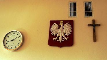 Godło i krzyż nad tablica w sali lekcyjnej wrocławskiego gimnazjum