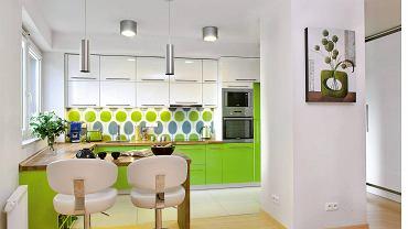 <B>Wygląda na to, że zabudowa w jednej barwie nieco się&#8200;nam&#8200;znudziła. Projektanci proponują więc kuchnie zaaranżowane w dwóch kolorach. Nie są monotonne, a jednocześnie nie nazbyt dynamiczne. Powinny więc zadowolić różne gusta.</B>  <BR />Właściciele tego mieszkania lubią intensywne barwy, dlatego ich wnętrza, łącznie z otwartą kuchnią, pulsują kolorami. Na fronty kuchennych mebli, zrobionych z lakierowanej na wysoki połysk płyty&#8200;MDF, wybrali żywą zieleń (szafki dolne) oraz łagodzącą ją biel (górne). Blat roboczy, połączony z barkiem-stołem, został wykonany z&#8200;olejowanego klejonego drewna dębu. Podłogę przy szafkach wykończono płytami polerowanego gresu. Sąsiaduje on z posadzką z prasowanego bambusa w słomkowym odcieniu, którą ułożono w pozostałych częściach mieszkania.