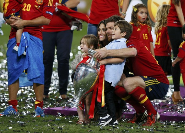 Spain's Xabi Alonso poses for a family photo after defeating Italy to win the Euro 2012 final soccer match at the Olympic stadium in Kiev, July 1, 2012.              REUTERS/Tony Gentile (UKRAINE  - Tags: SPORT SOCCER)