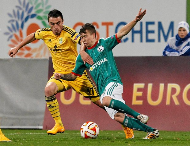 Legia Jakub Kosecki, right, challenges for the ball against Serhiy Pshenychnykh of Metalist  during a Europa League Group L soccer match between Metalist Kharkiv and  Legia Warsaw  at Lobanovskiy stadium in Kiev, Ukraine, Wednesday, Oct. 22, 2014. (AP Photo/Sergei Chuzavkov) ZDJĘCIE DO WKŁADKI: DGWRP Gazeta WyborczaSport