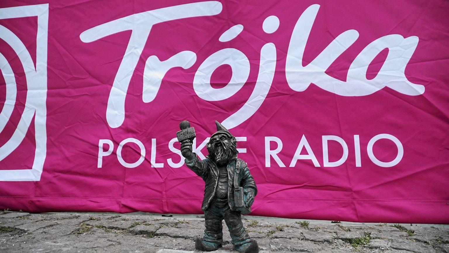 Trójkowy krasnal, za nim logo Programu Trzeciego Polskiego Radia