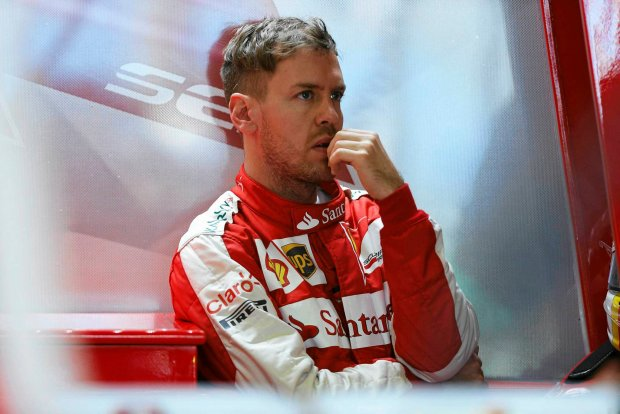 Ferrari Formula One driver Sebastian Vettel of Germany looks on in the team garage during the first practice session of the Australian F1 Grand Prix at the Albert Park circuit in Melbourne March 13, 2015. REUTERS/Brandon Malone (AUSTRALIA  - Tags: SPORT MOTORSPORT F1)   SLOWA KLUCZOWE: :rel:d:bm:SR1EB3D0CJS6N