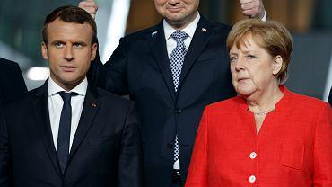 Szczyt NATO w Brukseli. Na pierwszym planie prezydent Francji Emmanuel Marcron oraz kanclerz Niemiec Angela Merkel. W głębi prezydent Andrzej Duda czyni charakterystyczny gest...