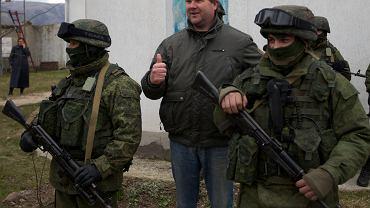 Ukraina, Krym - jeden z mieszkańców pozuje do zdjęć z tajemniczymi osobnikami z ugrupowania militarnego, które zajęło budynki rządowe na Krymie