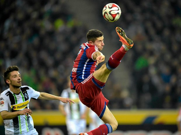 Bayern's Robert Lewandowski from Poland jumps for the ball during the German Bundesliga soccer match between Borussia Moenchengladbach and Bayern Munich in Moenchengladbach,  Germany, Sunday, Oct. 26, 2014. (AP Photo/Martin Meissner)