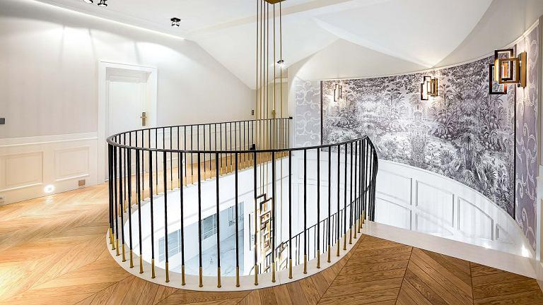 Imponujące schody wyłożone białym kwarcytem dostały prostą balustradę dyskretnie wykończoną mosiądzem. Na podłodze całego piętra leży parkiet ułożony we wzór jodły francuskiej. Półokrągłą ścianę zdobi wielkoformatowa grafika (ma 8 metrów długości) włoskiej marki Glamora, która przedstawia gęsty las - to luźne nawiązanie do sąsiadującej z domem Puszczy Knyszyńskiej.