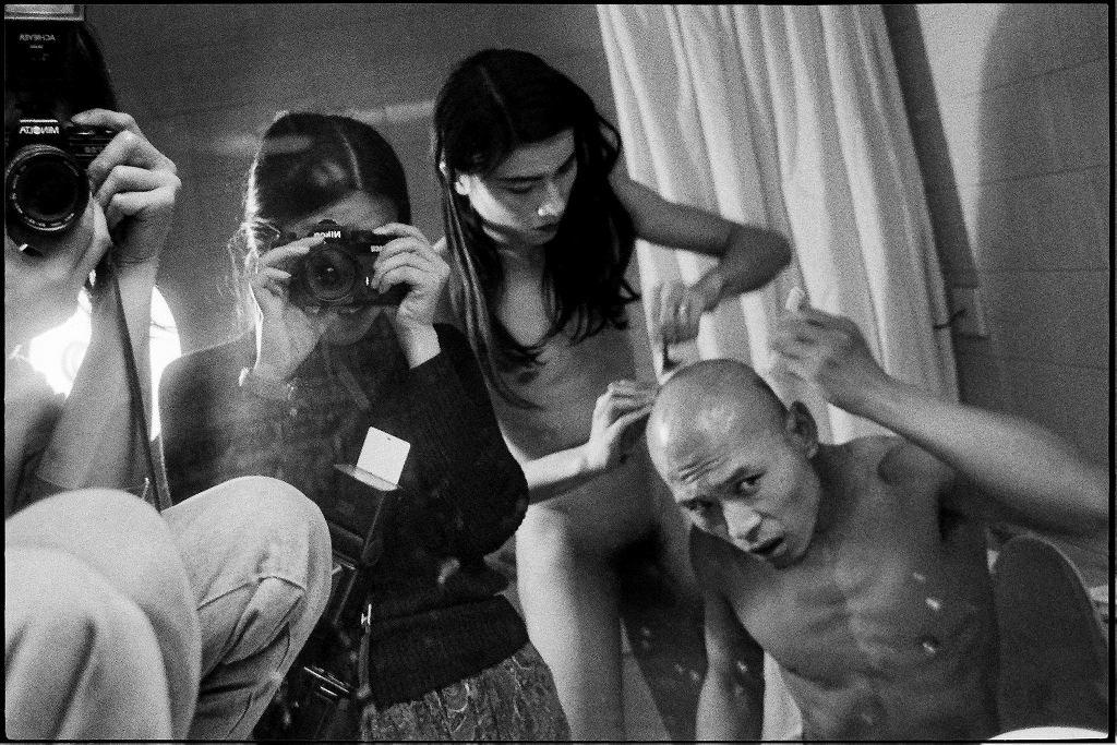 Danwen Xing fotografuje artystów Ma Liuminga i Zhang Huana podczas performansu 'Trzeci kontakt', Pekin 1994. / DANWEN XING