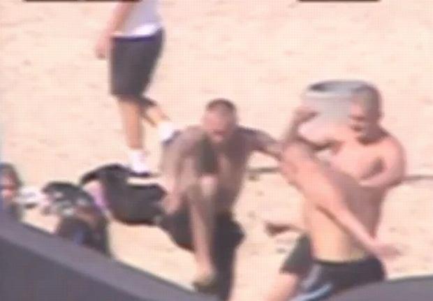Fragment nagrania z monitoringu: Ofiary nie widać. Mężczyźni kopią osobę, która leży na piasku
