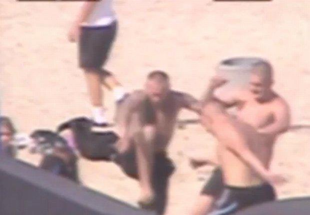 Fragment nagrania z monitoringu: Ofiary nie wida�. M�czy�ni kopi� osob�, kt�ra le�y na piasku