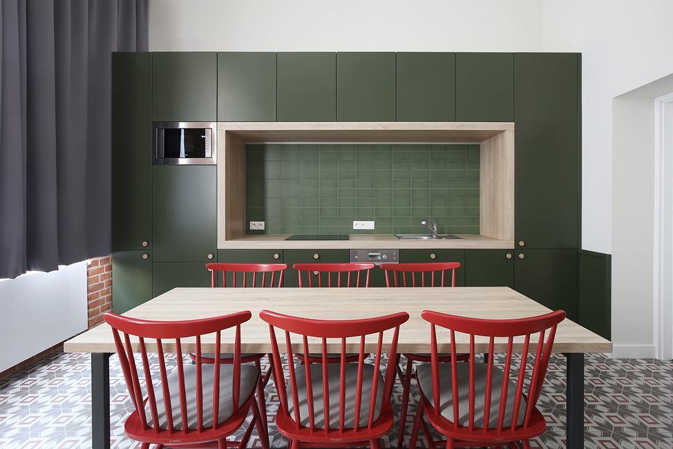 Na aranżację kuchni świetnie wpływa kontrast między zieloną zabudową, a czerwonymi krzesłami.