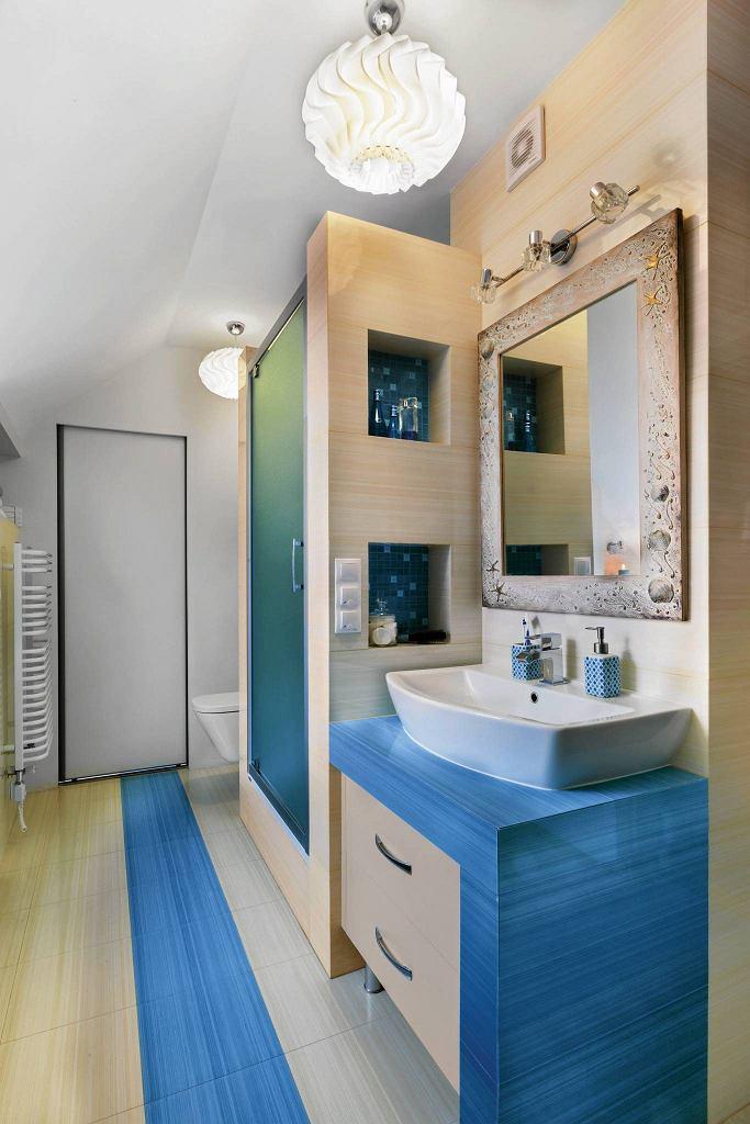 ZA MUROWANĄ KABINĄ PRYSZNICOWĄ dyskretnie ukryto podwieszony sedes. W łazience nie trzeba było szukać miejsca na pralkę - za przesuwanymi drzwiami znajduje się niewielkie pomieszczenie gospodarcze, które pełni m.in. funkcję domowej pralni.