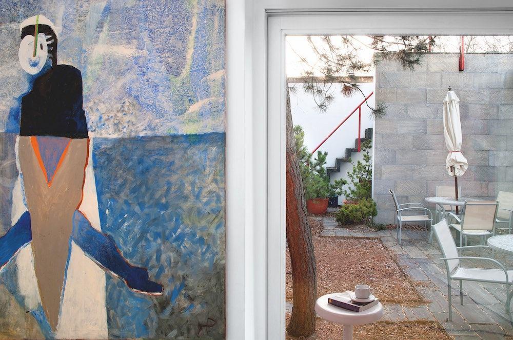 Utrzymane w stonowanych kolorach atrium ma betonowe schody z czerwoną poręczą. Kiedy w latach 70. powstawał projekt domu, w pierwszej wersji miało to być wejście na basen, jest taras. Po lewej: Obraz słynnej, nieżyjącej już malarki Teresy Pągowskiej pt. 'Widziany z wydmy'.