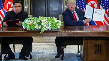 Donald Trump i Kim Dzong Un podpisują dokument podczas spotkania w Singapurze.