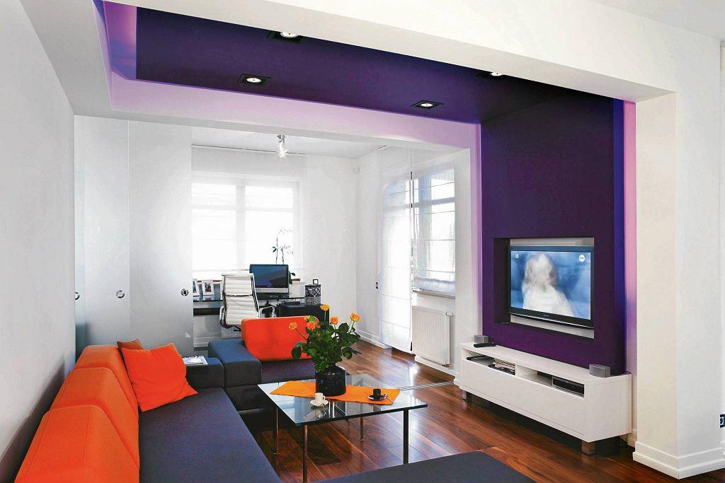 OŚWIETLENIE LEDOWE. DLA NASTROJU. Po obu stronach fioletowej ścianki (płyta gipsowo-kartonowa z wycięciem na telewizor) zainstalowano taśmy LED. Kolorowe światło zaznacza strefę wypoczynku.