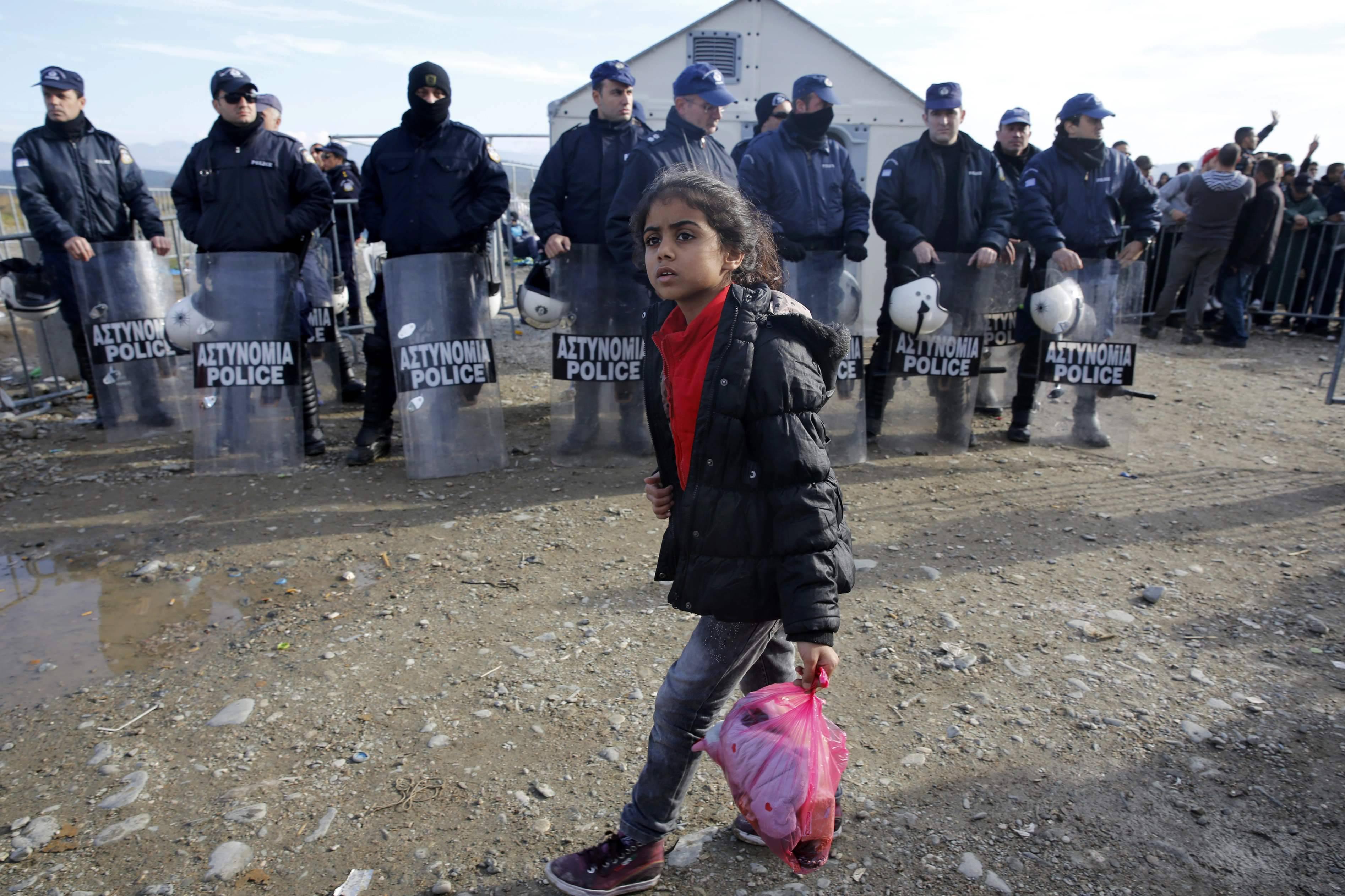 Syryjska dzieczynka na tle policjantów na granicy Grecji z Macedonią (fot. Yannis Behrakis / Reuters)