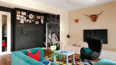 <B>SALON</B>. Na ścianę naklejono fototapetę ze zdjęciem dzieci gospodarzy mieszkania. Ścianę obok fototapety pomalowano magnetyczną farbą tablicową. Taka ściana nie musi służyć wyłącznie zabawie - może np. pełnić funkcję domowej tablicy ogłoszeniowej.