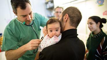Lekarz bada dziecko w ośrodku dla uchodźców na lotnisku Tempelhof w Berlinie