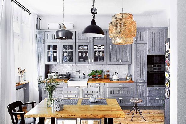 Szafki kuchenne zlitego drewna zrobił tata projektantki, który prowadzi firmę Meble Kuboth. Żłobienia na frontach iporcelanowe uchwyty dodają im stylu.
