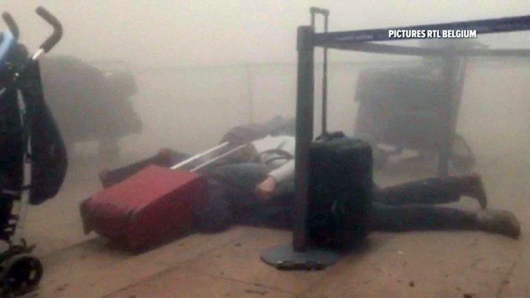 Kadr z lotniska chwilę po zamachu z belgijskiej TV RTL. Podróżni leżą na podłodze w chmurze pyłu po eksplozji