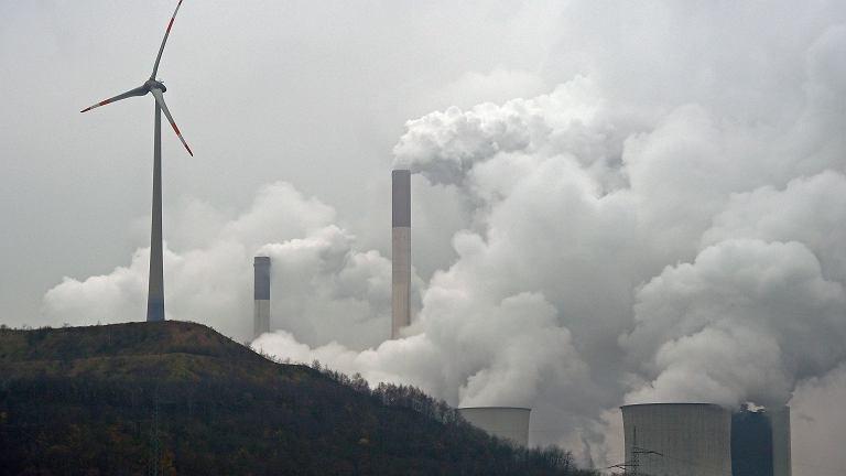 Wiatrak na tle elektrowni węglowej w Gelsenkirchen w Niemczech