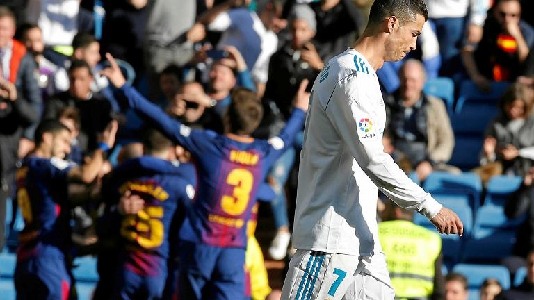 Real Madrid's Cristiano Ronaldo walks past as Barcelona players celebrate scoring their 3rd goal during a Spanish La Liga soccer match between Real Madrid and Barcelona