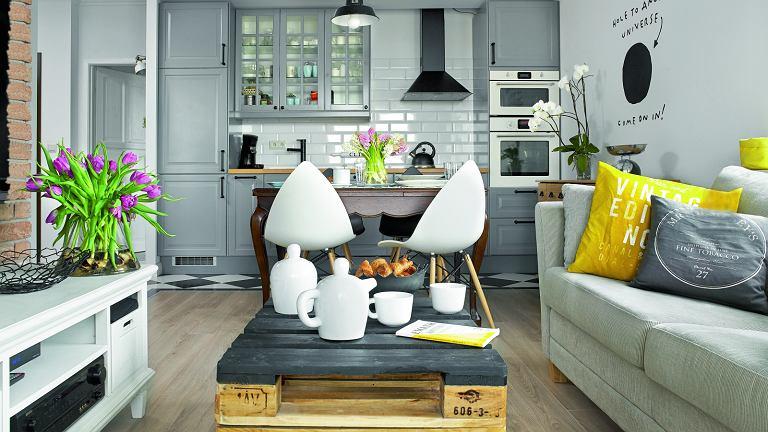 Europalety na salonach - stolik kawowy to dzieło Tomka, który po godzinach lubi poszaleć zmłotkiem iwiertarką. Szafkę pod telewizor właściciele kupili w meblarnia.com.pl, kanapę wsklepie Inne Meble (stąd jest  też zastawa).