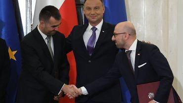 Prezydent RP Andrzej Duda z nowym rzecznikiem Błażejem Spychalskim i ustępującym z funkcji Krzysztofem Łapińskim podczas uroczystości w pałacu prezydenckim, 7 września 2018.