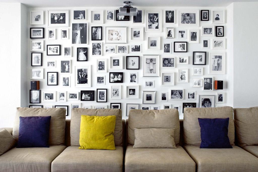 WYKORZYSTAJ NIEWYKORZYSTANE. Pomysł na ciekawą aranżację dużej wnęki (albo całej ściany). Klasyczne półki, którymi zwykle zabudowuje się takie miejsca, zastąp kolekcją fotografii. Będzie stanowić niebanalne tło kanapy, foteli lub stołu.