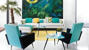 Kolorystyka wnętrza dostraja się do ściennego pejzażu tropikalnej dżungli. Chris zamówiła obraz u znajomej malarki i konserwatorki Dorel Chiras. Poduszki w tkaninach Designers Guild, fotele z lat 60.; dywan Stockholm (IKEA).