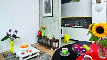 Kuchnię od pokoju dziennego oddziela tylko fragment ściany. Dzięki temu jest dobrze doświetlona, a jednocześnie wyraźnie wyodrębniona z reszty pomieszczenia.