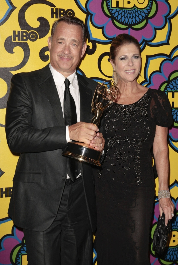 "Producer Tom Hanks holds his Emmy for outstanding miniseries or movie for the political film ""Game Change"" as he arrives with his wife Rita Wilson at HBO's post award reception following the 64th Primetime Emmy Awards in West Hollywood, California September 23, 2012. REUTERS/Jason Redmond  (UNITED STATES - Tags: ENTERTAINMENT)"