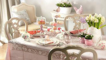 Świąteczny posiłek wymaga odpowiedniej oprawy. Nie masz pomysłu, jak udekorować stół? Zobacz dwie propozycje naszych stylistek. <BR />DEKORACJE ŚWIĄTECZNE - STÓŁ. <b>Romantycznie.</b> W czystym świetle wiosennego poranka nikt nie przeoczy urody delikatnych koronek, a blask ozdobnych naczyń i figurek w starym stylu oraz pastelowe kolory zachwycą gości wielkanocnego śniadania. Zapowiada się długie biesiadowanie. <BR />Talerze obiadowe - 49 zł/szt., talerze deserowe - 28 zł/szt. Almi Decor; serwetki - 33 zł/szt., obrączki na serwetki - 43 zł/szt., Ludwik Styl; sztućce - 7,50 zł/szt., wazon - 49 zł, świecznik (kwiat) - 45 zł, home&you; patera piętrowa - 69,90 zł, tendom.pl; cukiernica - 140 zł, Q Forma;  patera z kloszem  - 79 zł, szklanki - 49 zł/6 szt., westwing.pl; ptaszek (na paterze) - 25 zł, zajączek (biały) - 35 zł, zajączek (w róże) - 49 zł, kura - 59 zł, zajączek (przy cukiernicy) - 12 zł, Meubles de Charme; obrus - własność stylistki; stół, krzesła, konsolka, fotel, poduszka - na zamówienie, Meubles de Charme. Kwiaty do sesji dostarczyła warszawska kwiaciarnia Bukieciarnia