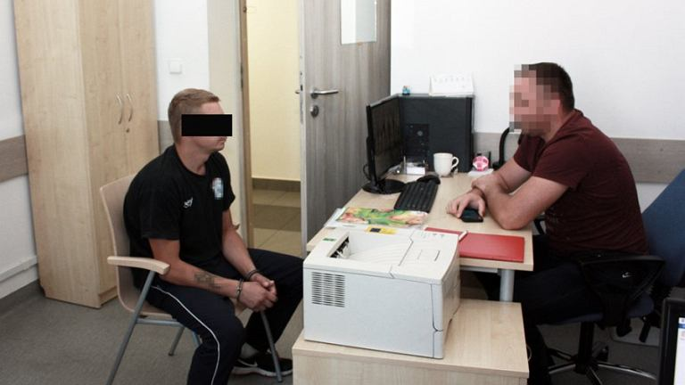 Policjant wykonuje czynności z podejrzanym Krystianem K.
