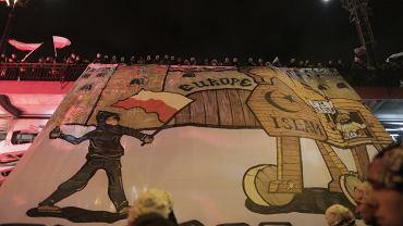 Marsz Niepodległości organizowany przez skrajnych prawicowców. Z mostu Poniatowskiego zwieszono baner przedstawiający Europę jako zamek i konia trojańskiego z uchodźcami. Obok wizerunek narodowca, który rzuca koktajl Mołotowa. Zapłonęły race i skandowano: 'Cała Polska śpiewa z nami, wypierdalać z uchodźcami!'