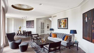 Okrągła lampa w salonie (ma 2 metry średnicy) pokryta płatkami srebra nawiązuje do kształtu klatki schodowej i spiralnie skręconych schodów. W tle po prawej drzwi wejściowe do apartamentu (w mieszkaniu są jeszcze drugie, które prowadzą do kuchni i części prywatnej).