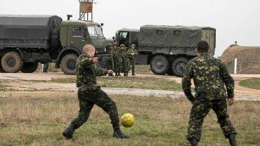 Rosyjscy żołnierze obserwują ukraińskich, którzy grają w piłkę