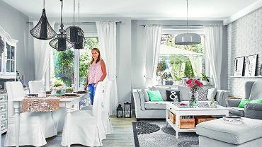 Ciemny stary kredens od teściów właścicielka przemalowała na biało. Do niego dobrała stół i krzesła z IKEA w tym samym kolorze, a całość przełamała czarnymi lampami ze sklepu Nowodvorski Lighting. Kanapa jest z MTI Furninova, dywan - z IKEA, żyrandol - również z firmy Nowodvorski Lighting. Podłoga to płytki ceramiczne imitujące drewno (marki Imola); gospodyni sama zadecydowała, jak mają być ułożone.