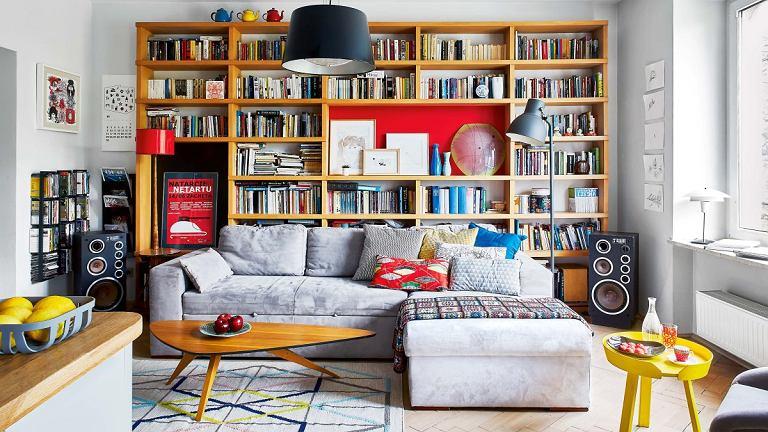 Stare i nowe wzornictwo widealnej harmonii. Stolik oorganicznej formie, lampa podłogowa zlat sześćdziesiątych XX wieku (ocalona zpobliskiego śmietnika) towarzyszą współczesnej kanapie idywanowi zkolekcji IKEA Stockholm 2017. Żółty stolik Around idesignerski koszyk na cytryny to przykłady nowoczesnego wzornictwa duńskiej marki Muuto (Scandinavian Living). Wykonana na zamówienie biblioteczka służy także jako miejsce eksponowania ceramiki oraz rysunków polskich ilustratorów: Agaty 'Endo' Nowickiej, Arobala iAgaty Bogackiej.