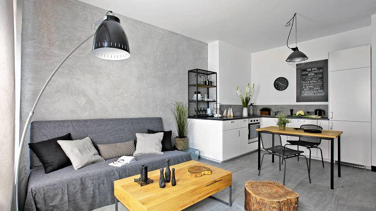 Otwarta kuchnia i sąsiadujący z nią pokój tworzą w miarę przestronną strefę dzienną. Do kuchni wybrano zabudowę w kolorze ścian, by nie dominowała nad częścią wypoczynkową.