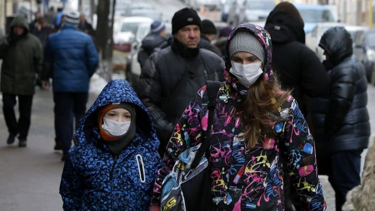 Ludzie w maskach na ulicach Kijowa