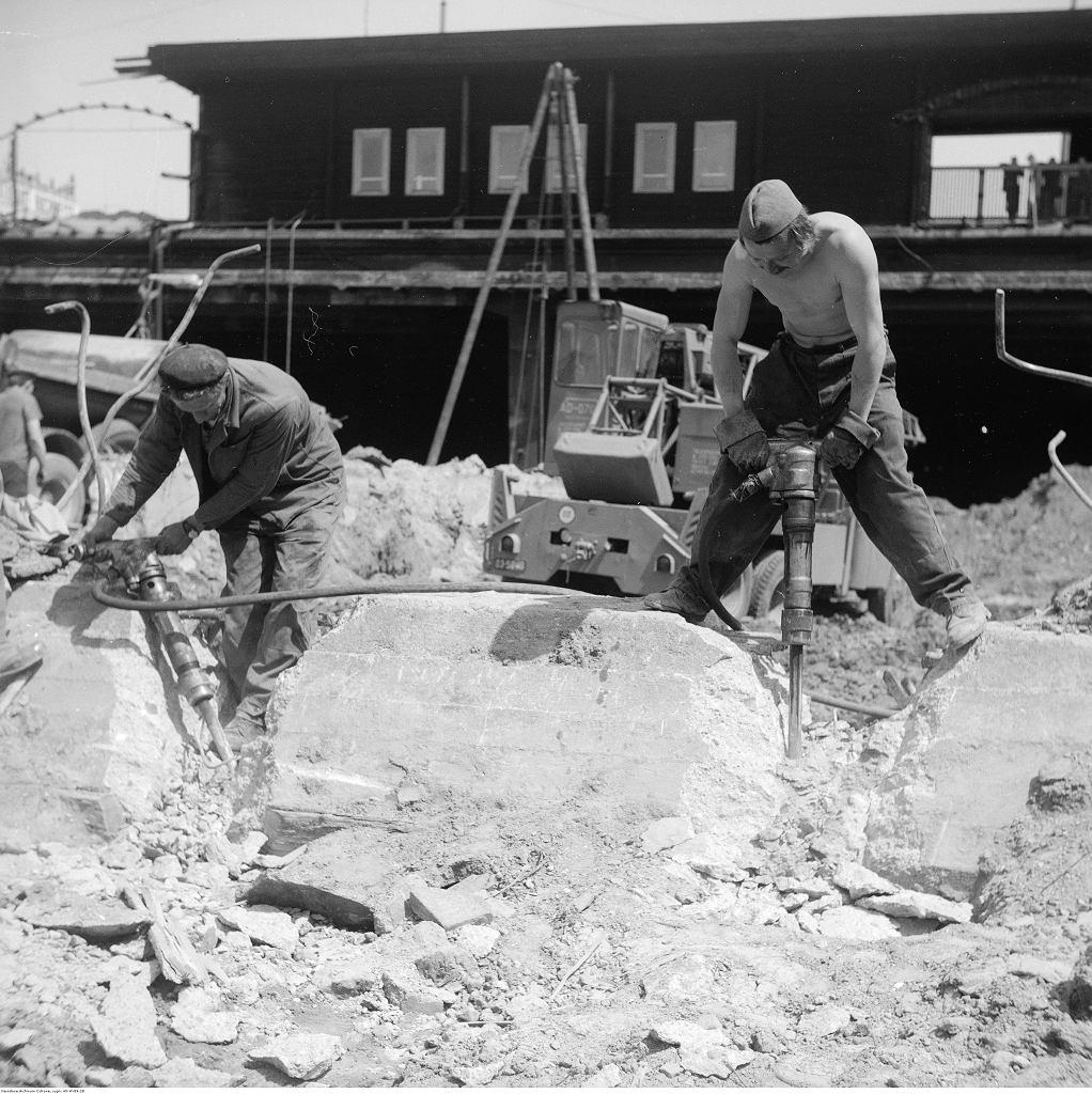 Robotnicy z młotami pneumatycznymi kruszą betonowe elementy. W tle hala prowizorycznego dworca, pełniącego funkcje Dworca Centralnego przed ukończeniem budowy. 1974 r.